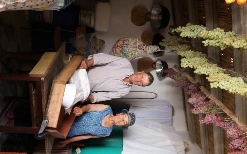 """António Gonçalves e Maria Henriques com a sua """"burra"""", utensílio de madeira usado para fazer vinho à mão, e com uva a secar (e tomate também) (Mealha, freguesia de Cachopo). © Município de Tavira 2017"""
